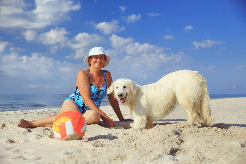 Bejaarde met haar golderretriever op een overzees stock foto's