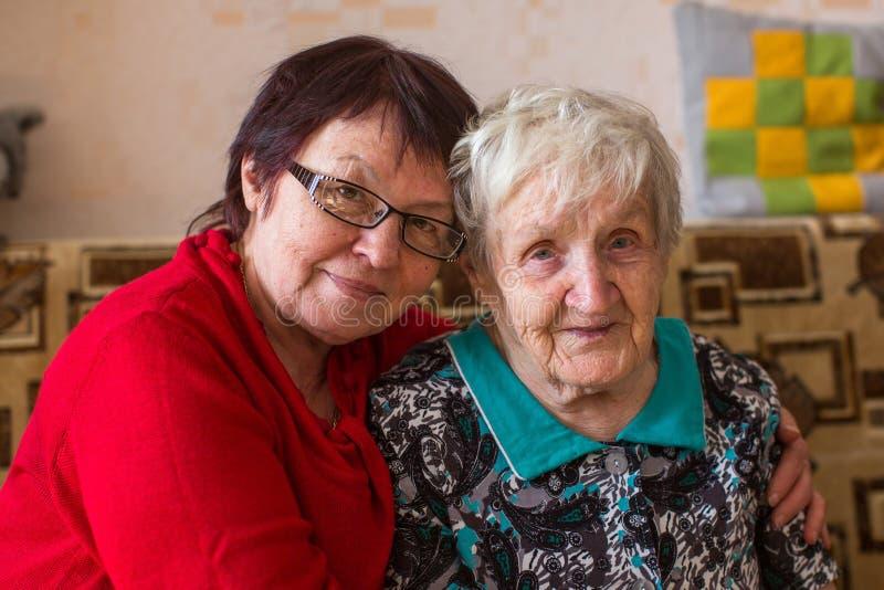 Bejaarde met haar volwassen dochter op de laag Liefde stock foto