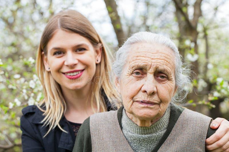 Bejaarde met haar werker uit de hulpverlening openlucht stock afbeeldingen