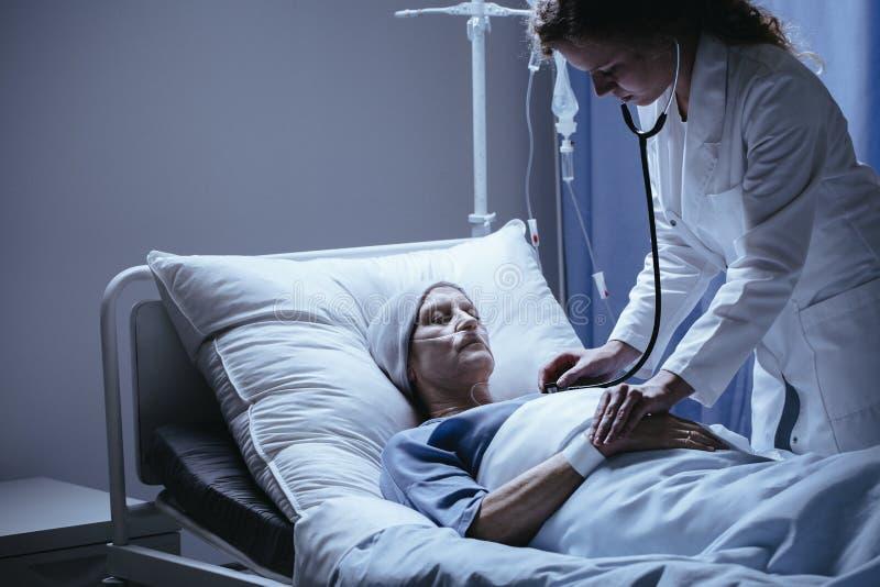 Bejaarde met headscarf in het ziekenhuisbed terwijl artsenchecki royalty-vrije stock fotografie