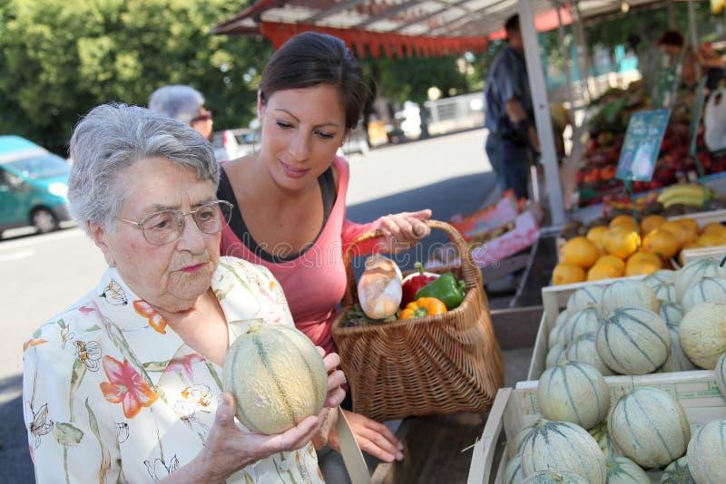 Bejaarde met homecarer bij de markt royalty-vrije stock foto