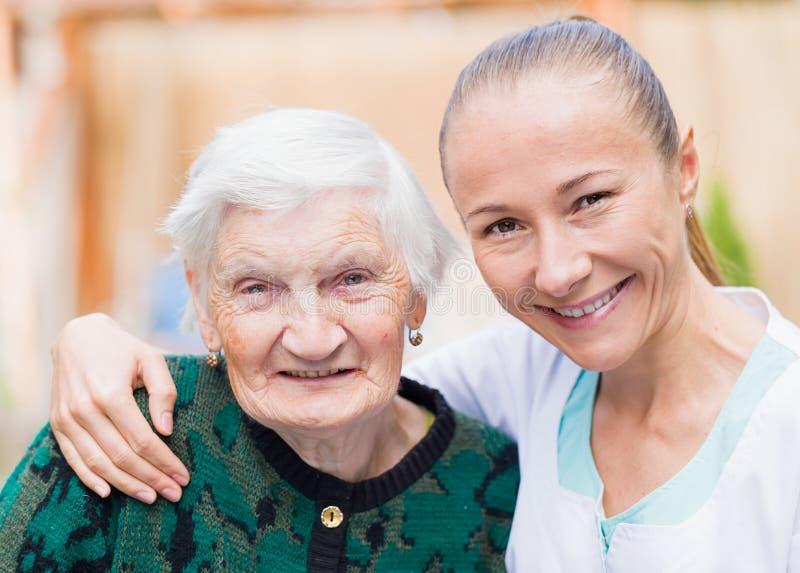 Bejaarde met verzorger stock afbeelding