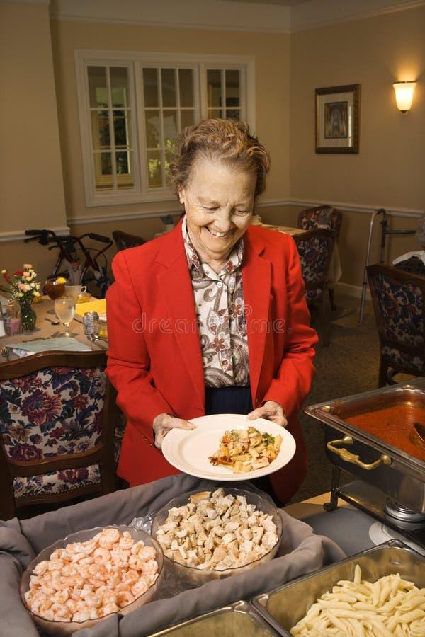 Bejaarde met voedsel. stock foto
