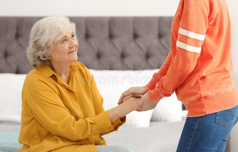 Bejaarde met vrouwelijke verzorger stock fotografie