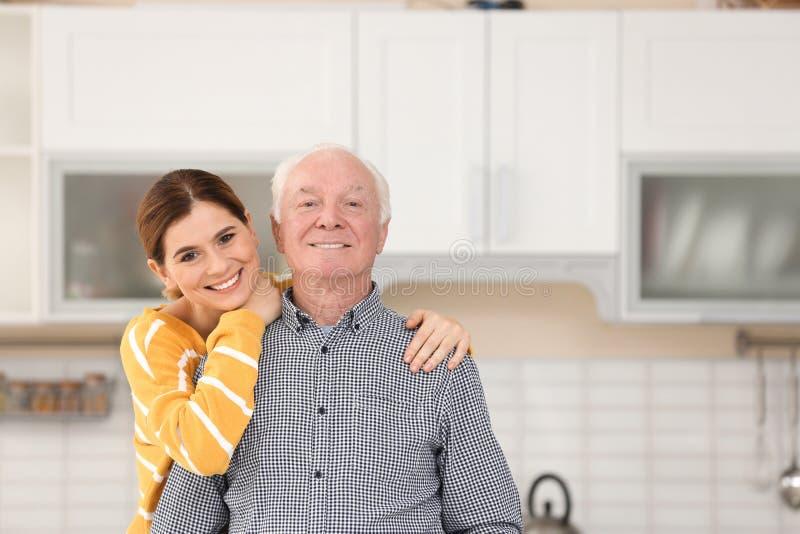 Bejaarde met vrouwelijke verzorger in keuken royalty-vrije stock afbeeldingen