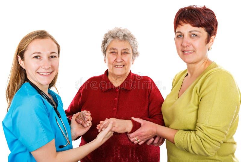 Bejaarde met werker uit de hulpverlening en de jonge arts stock afbeelding