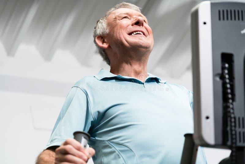 Bejaarde opleiding op dwarstrainer bij de gymnastiek royalty-vrije stock afbeelding