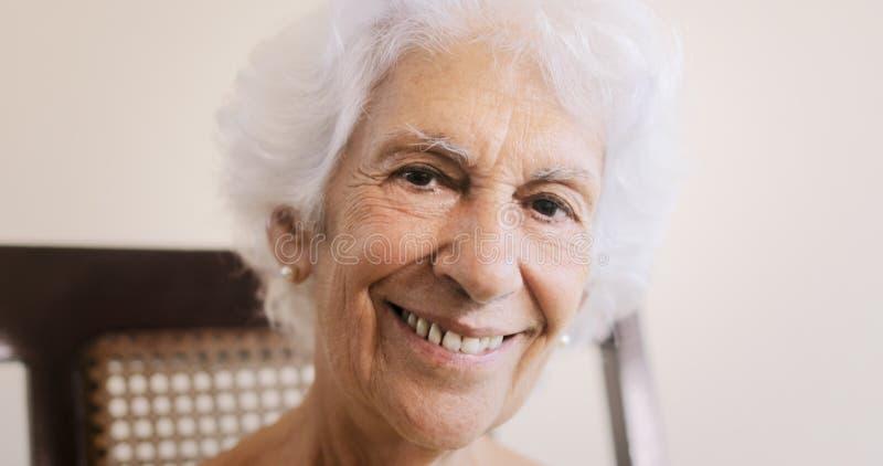Bejaarde Oude Dame Relaxing On Rocking Stoel thuis stock afbeeldingen