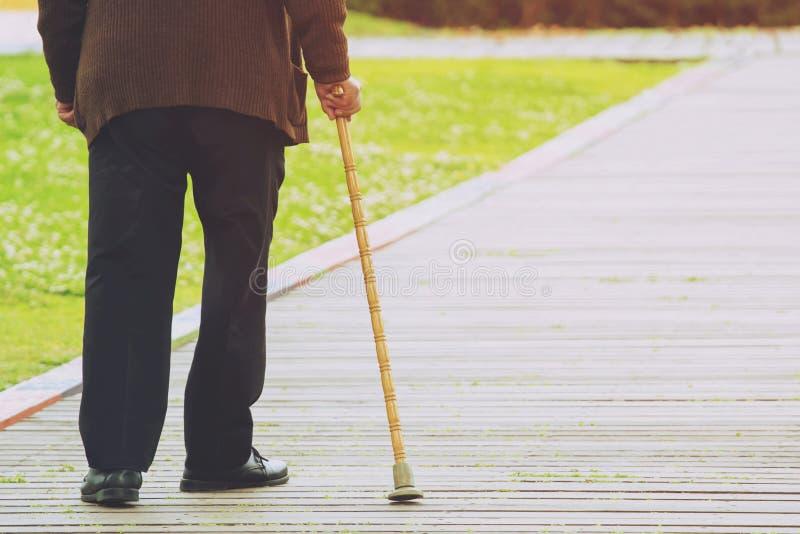 Bejaarde oude mens die met wandelstoktribune bij voetpadstoep de kruising wacht stock afbeeldingen