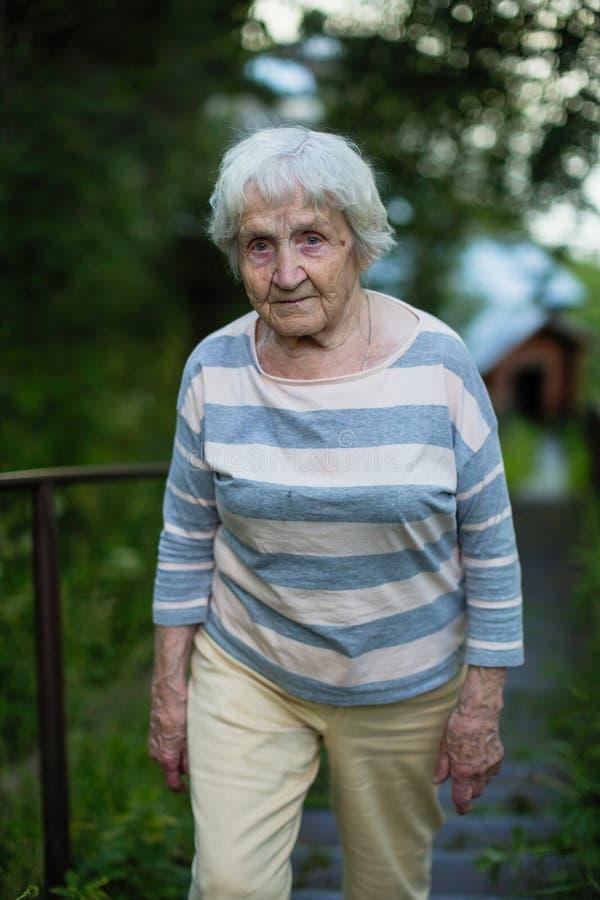 Bejaarde oude vrouwengangen in een de zomerpark stock fotografie