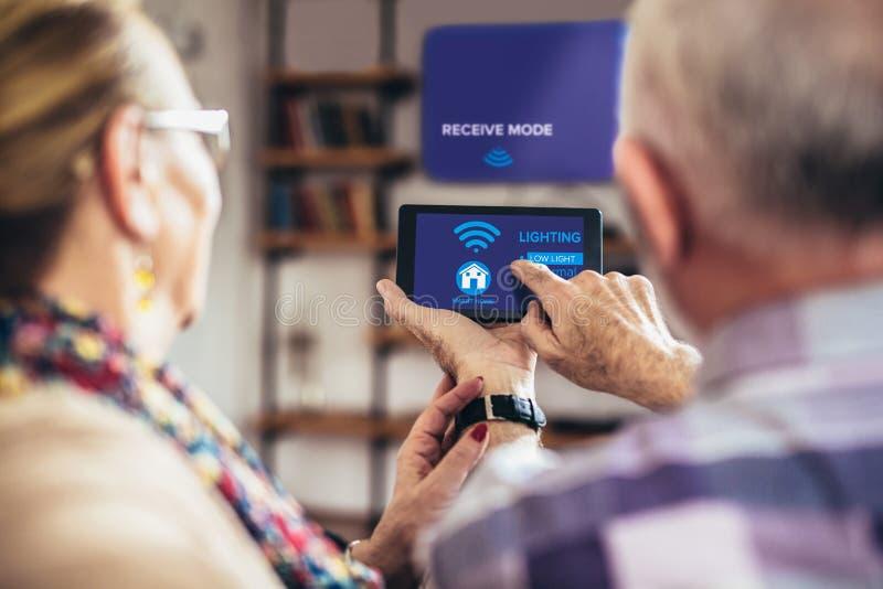 Bejaarde paarzitting comfortabel op een bank met hun ruggen die het systeem van het afstandsbedieninghuis holiding royalty-vrije stock afbeeldingen