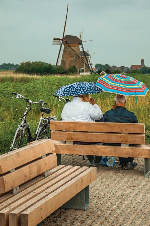 Bejaarde paarzitting het letten op gebieden en windmolen in Kinderdijk stock foto's
