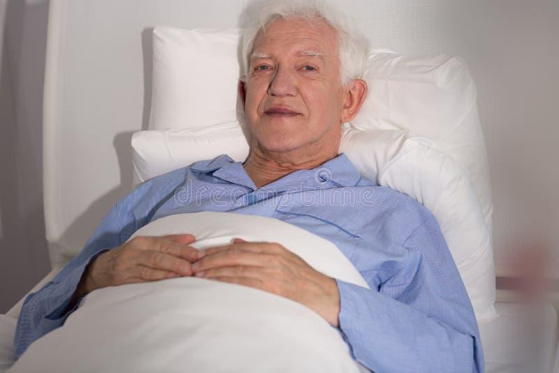 Bejaarde patiënt in bed stock afbeelding