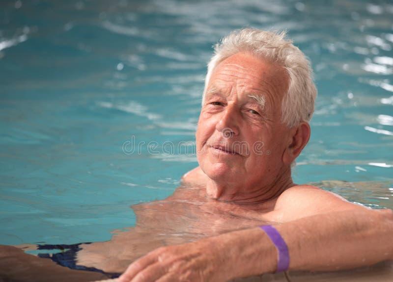 Bejaarde in pool stock foto