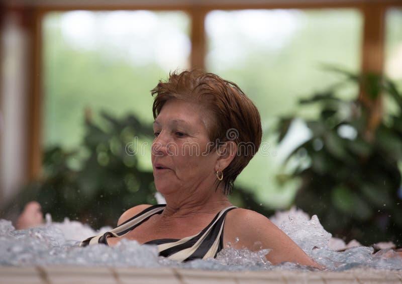 Bejaarde in pool stock foto's
