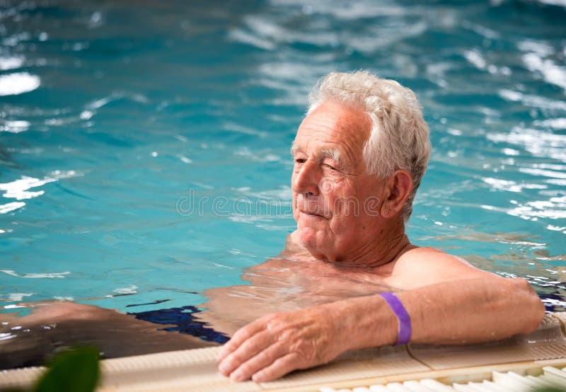 Bejaarde in pool stock fotografie