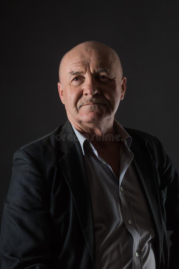 Bejaarde positieve mannelijke zakenman op een donkere achtergrond royalty-vrije stock afbeeldingen