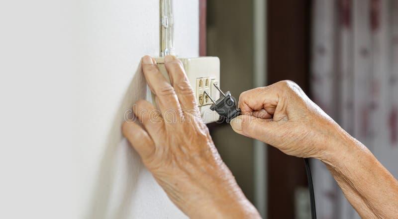 Bejaarde proberende stopkabel aan de elektrische afzet stock afbeelding