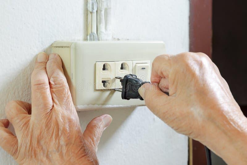 Bejaarde proberende stopkabel aan de elektrische afzet stock foto