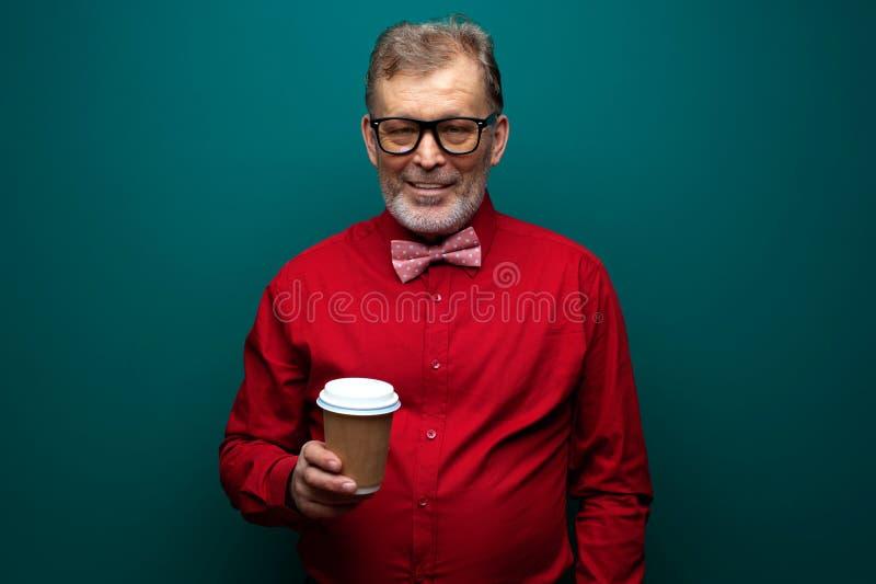 Bejaarde in rood overhemd met de koffie van de vlinderdasgreep royalty-vrije stock fotografie