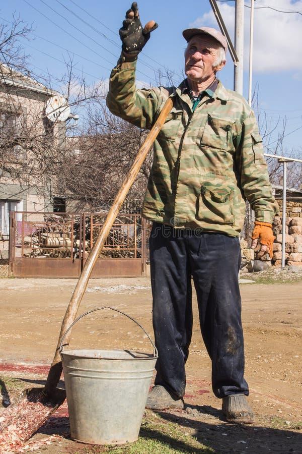 Bejaarde Russische landbouwer met emmer royalty-vrije stock fotografie