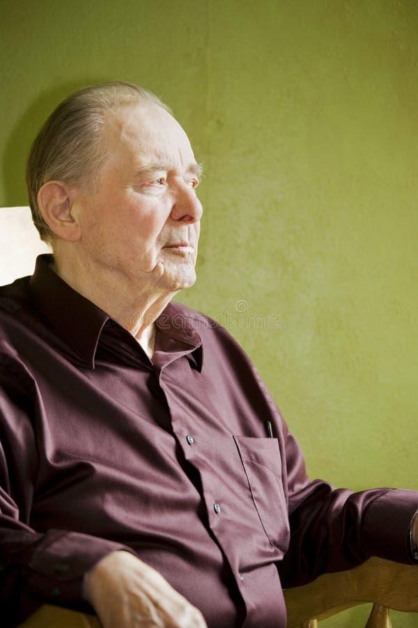 Bejaarde in schommelstoel stock fotografie