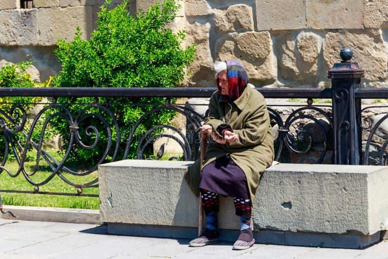 Bejaarde slechte vrouw die aalmoes in de straat bedelen dichtbij een tempel royalty-vrije stock foto's