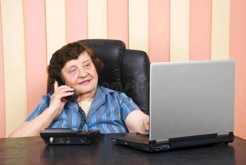 Bejaarde stafmedewerker laptoop en bespreking die telefonisch gebruiken royalty-vrije stock afbeeldingen