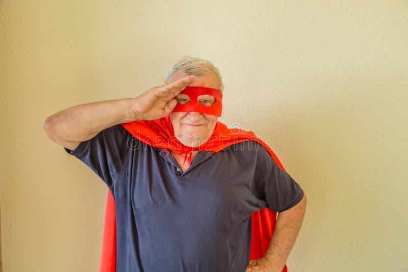 Bejaarde superhero die een militaire begroeting doen royalty-vrije stock foto