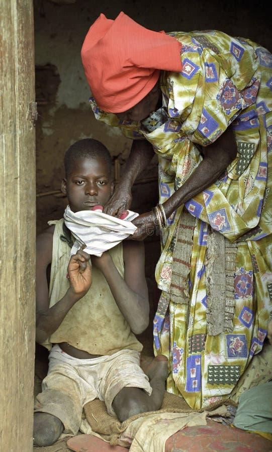 Bejaarde Ugandan vrouwenzorgen voor kleinkind stock foto's