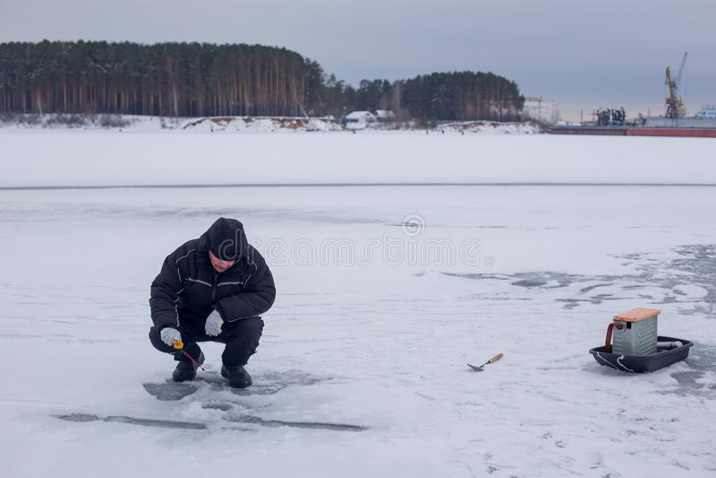 Bejaarde visser die in donkere kleren op de winterhengel vissen op bevroren rivier royalty-vrije stock foto
