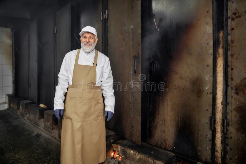 Bejaarde vrolijke slager, arbeider van rookhok het stellen stock afbeelding