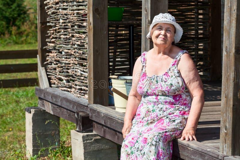 Bejaarde vrolijke vrouwenzitting dichtbij eigen huis royalty-vrije stock foto