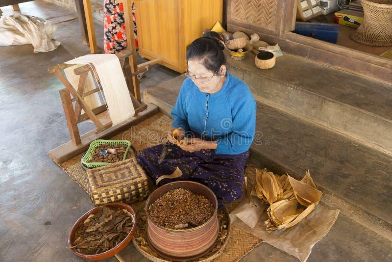 Bejaarde vrouwelijke werknemerzitting met verschillende ingrediënten die op smaak gebrachte sigaren rollen stock fotografie