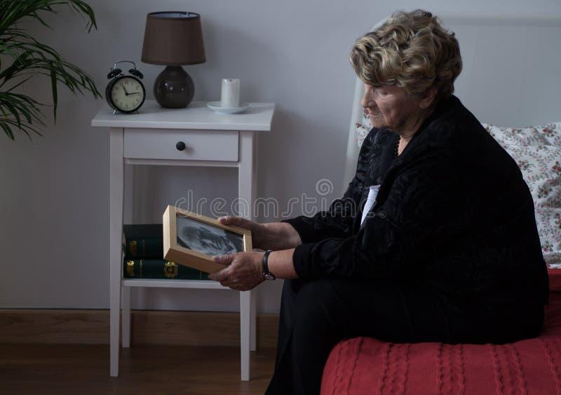 Bejaarde weduwe geworden dame in zorg stock afbeelding
