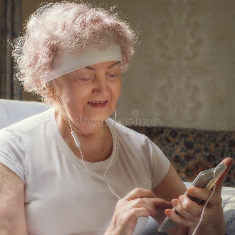 Bejaarde womElderly vrouw die aan muziek met een glimlach luisteren Rust na het fitnessan luisteren aan muziek met een glimlach R stock afbeelding
