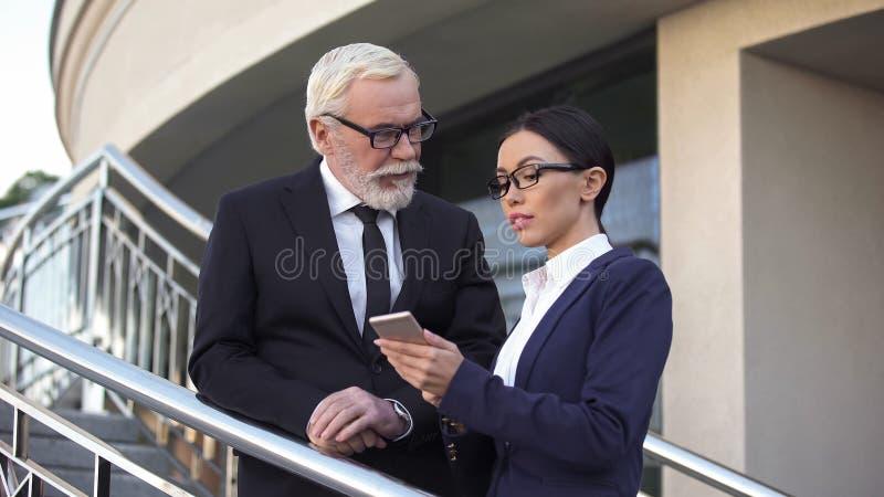 Bejaarde zakenman die met aantrekkelijke secretaresse, vrouw flirten die over het werk spreken stock foto's