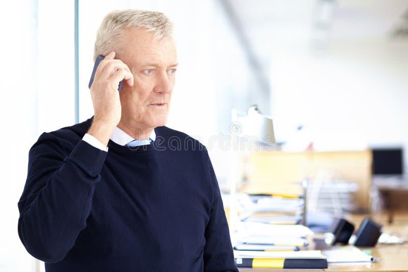 Bejaarde zakenman die met somebody op zijn celtelefoon spreken terwijl status in het bureau royalty-vrije stock afbeelding