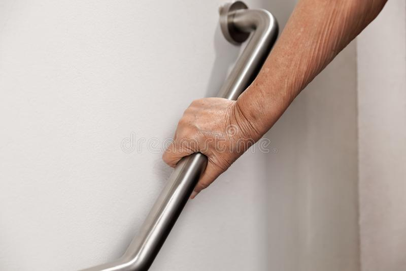 Bejaardeholding op leuning voor veiligheidsstappen royalty-vrije stock afbeeldingen