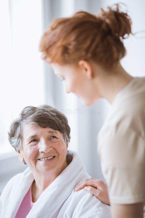 Bejaarden in badjas en jonge vrijwilliger bij verpleeghuis royalty-vrije stock afbeeldingen