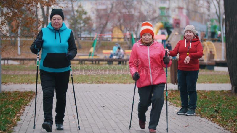 Bejaarden die op stokken van het noordse lopen op een stoep lopen stock foto