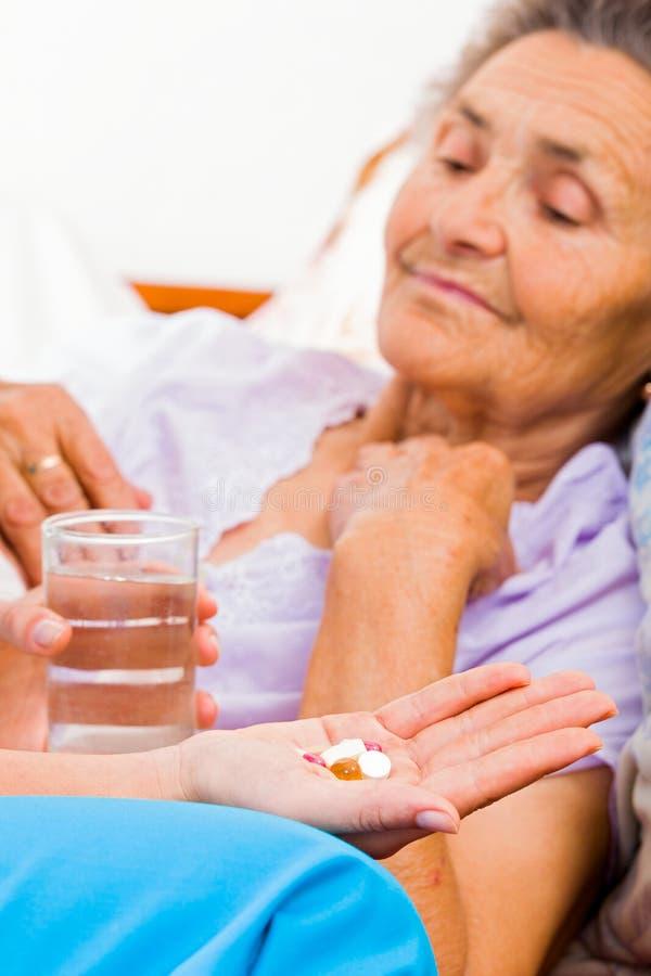 Bejaarden die Pillen nemen stock foto
