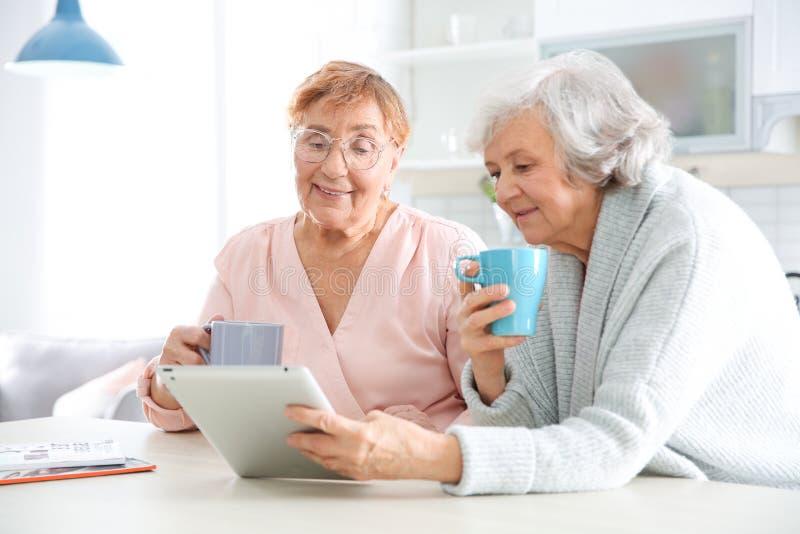 Bejaarden die tabletpc met behulp van bij lijst royalty-vrije stock foto's