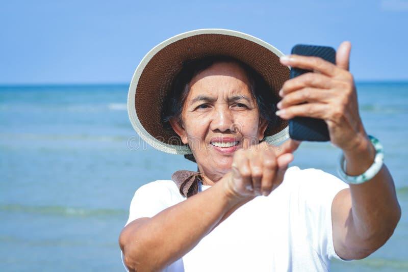 Bejaarden die telefoons houden om beelden te nemen stock foto's