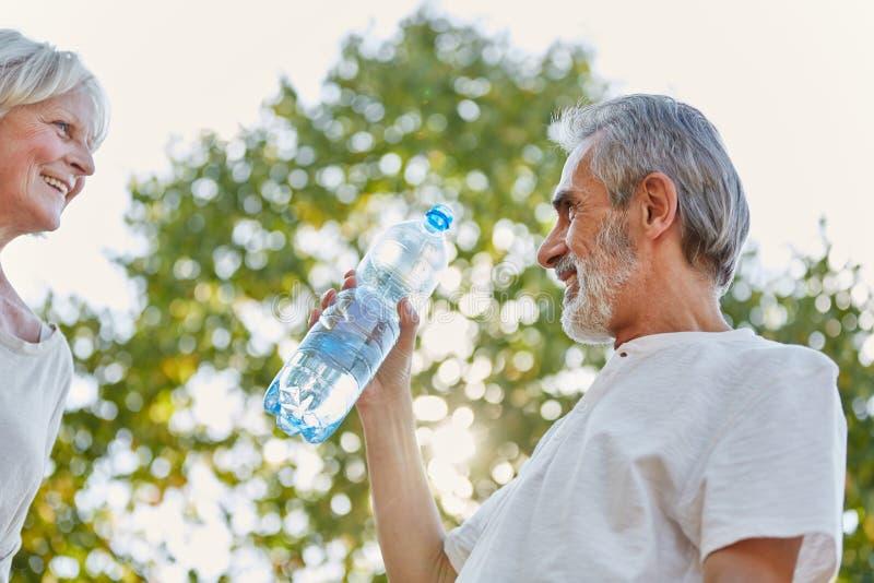 Bejaarden die van een waterfles drinken royalty-vrije stock afbeelding