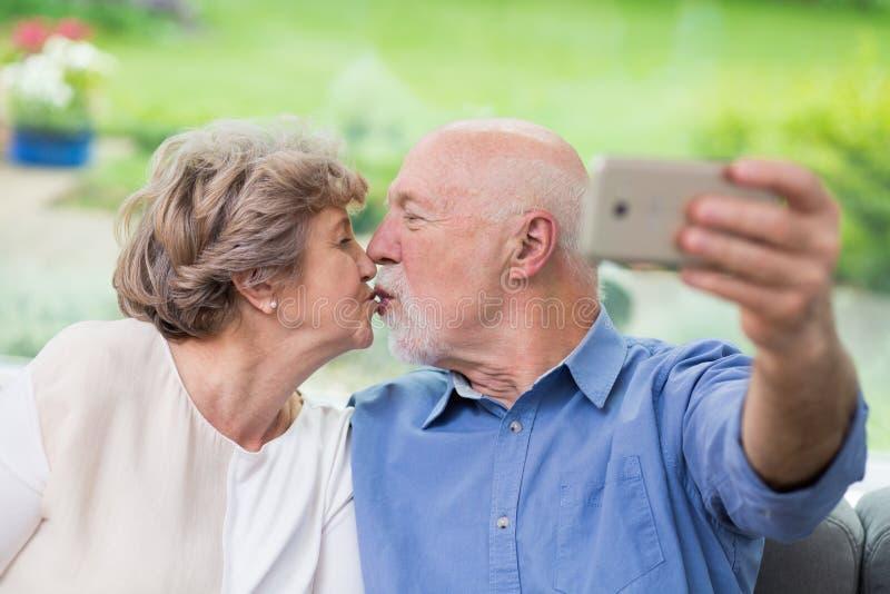 bejaarden die zoenen voor een mobiele telefoon terwijl ze selfie innemen stock fotografie