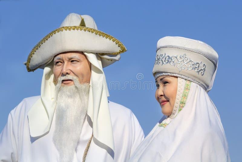 Bejaarden en vrouwen in witte nationale Kazakh kleren tegen de achtergrond van de hemel tijdens de Carnaval-vakantie royalty-vrije stock foto's