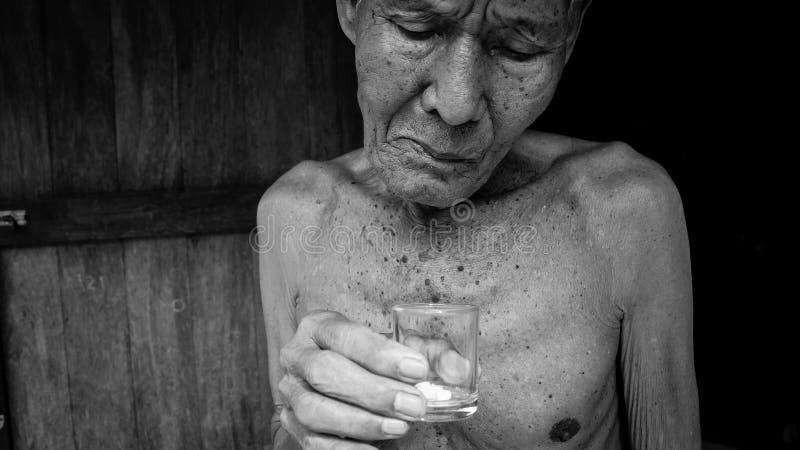 Bejaarden van het nemen van pillen worden vermoeid die stock foto
