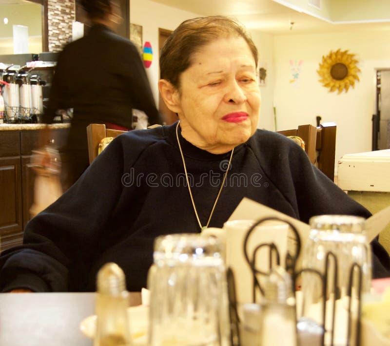 Bejaardezitting in een eetkamer die een menu lezen royalty-vrije stock foto's