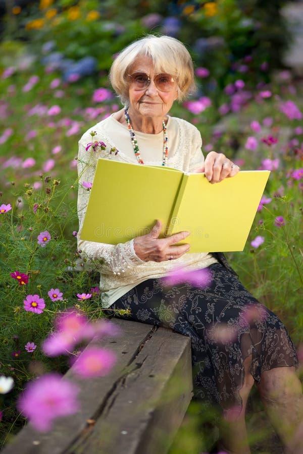 Bejaardezitting in haar tuin met een boek stock foto's